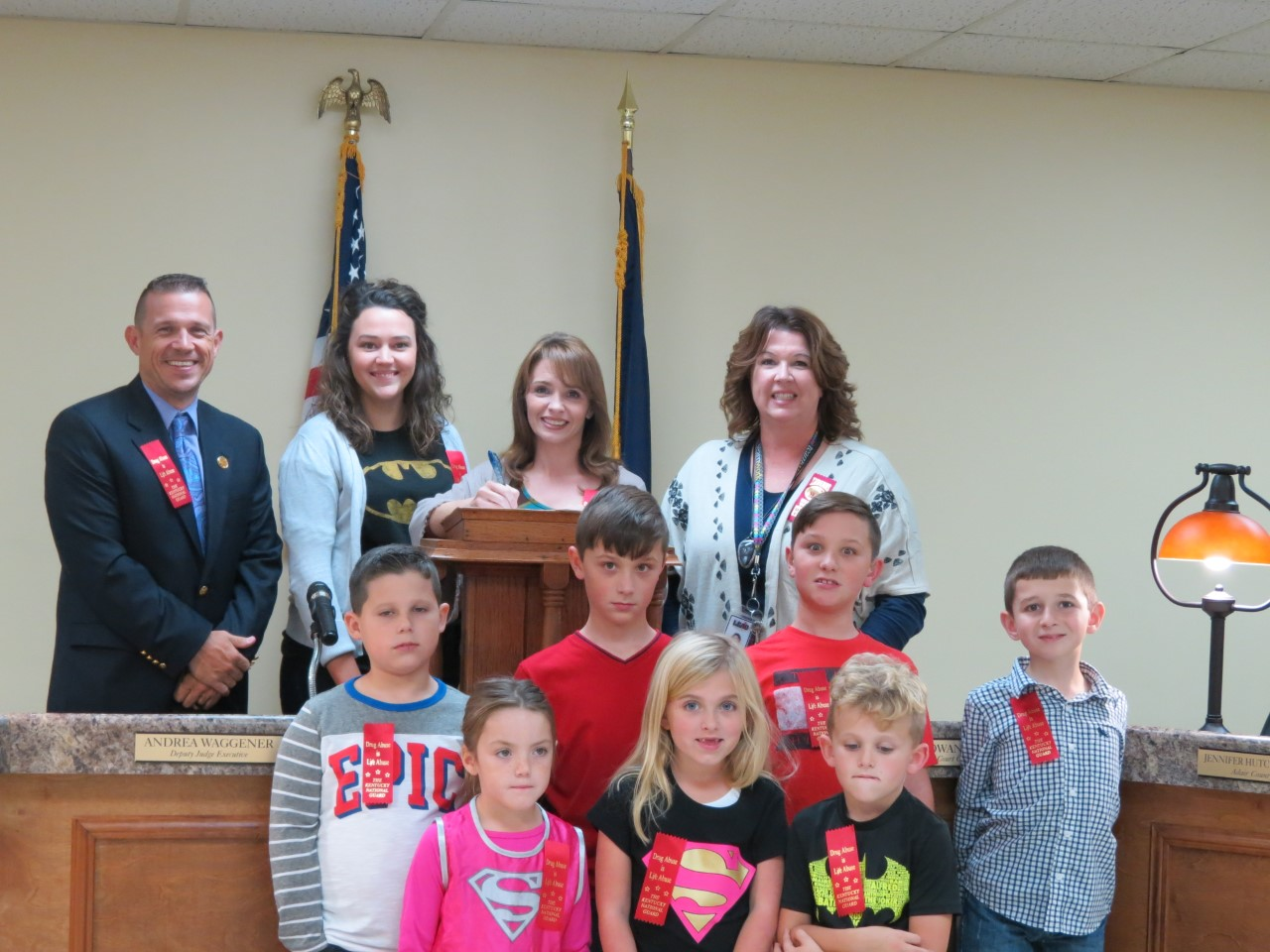 Adair County School staff, Robbie Harmon, Sarah Dean and Debbie Cowan join Deputy Judge Executive Andrea Waggener and students Jay Harmon, Colt King, Cooper King, Tyler Grant, Molly Froedge, Virginia Willis and George Willis in signing a proclamation declaring the week of October 23rd - 27th as Red Ribbon Week for Adair County.